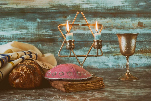 Bougies de la veille de shabbat et tasse de vin avec pain challah couvert,