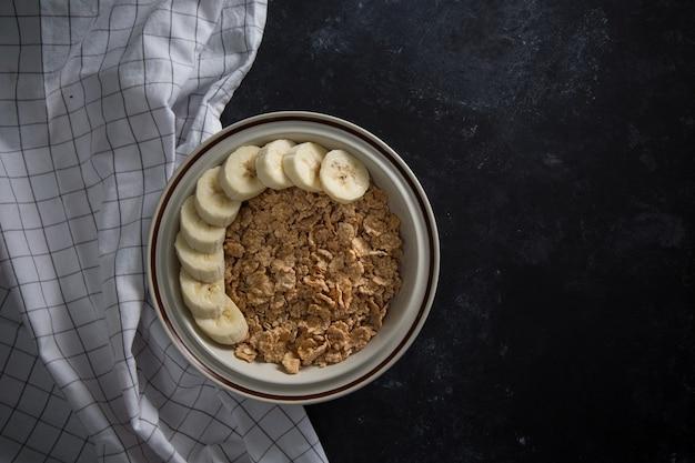 Bouillie d'avoine saine biologique avec des bananes fraîches. le bol en porcelaine blanche avec serviette
