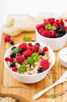 Bouillie d'avoine savoureuse et saine avec des baies, des graines de lin et du yaourt. petit-déjeuner sain. nutrition adéquat