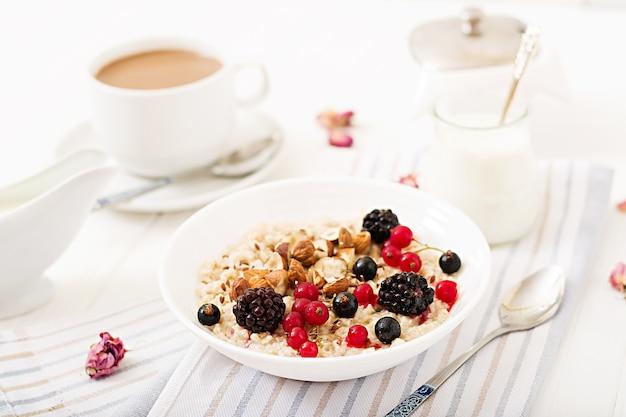 Bouillie d'avoine savoureuse et saine avec des baies, des graines de lin et des noix. petit-déjeuner sain.