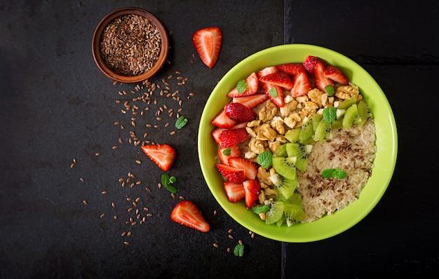 Bouillie d'avoine savoureuse et saine avec des baies, des noix et des graines de lin. petit-déjeuner sain. nourriture de fitness. nutrition adéquat. mise à plat. vue de dessus