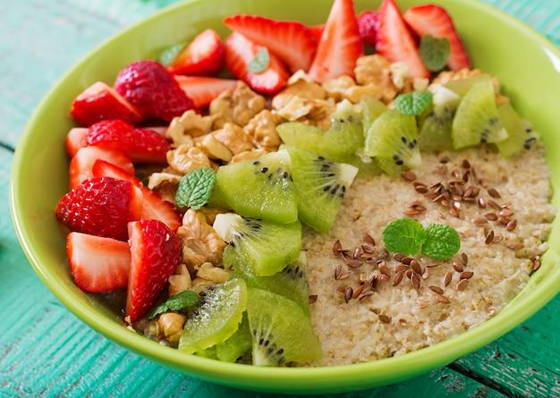 Bouillie d'avoine savoureuse et saine avec des baies, des noix et des graines de lin. petit-déjeuner sain. nourriture de fitness. nutrition adéquat