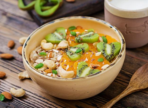 Bouillie d'avoine savoureuse et saine avec des fruits, des baies et des noix. petit-déjeuner sain. nutrition adéquat