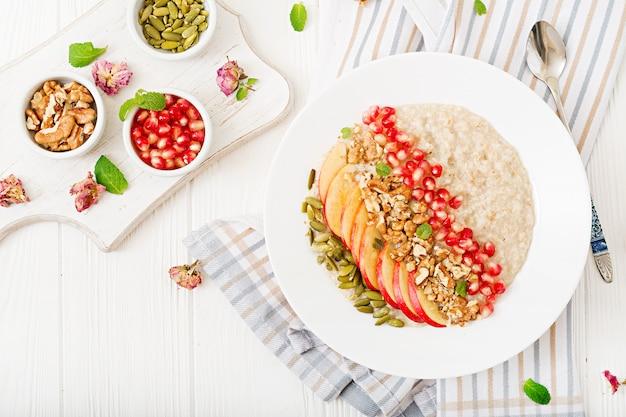 Bouillie d'avoine savoureuse et saine avec des pommes, de la grenade et des noix. petit-déjeuner sain. nourriture de fitness. nutrition adéquat. vue de dessus.
