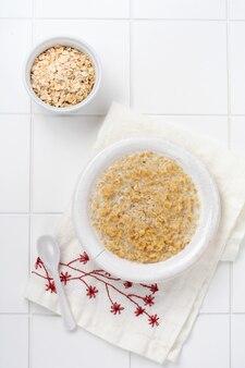 Bouillie d'avoine simple avec des fraises dans une assiette blanche sur une serviette en lin. concept d'aliments santé pour le petit-déjeuner. vue de dessus