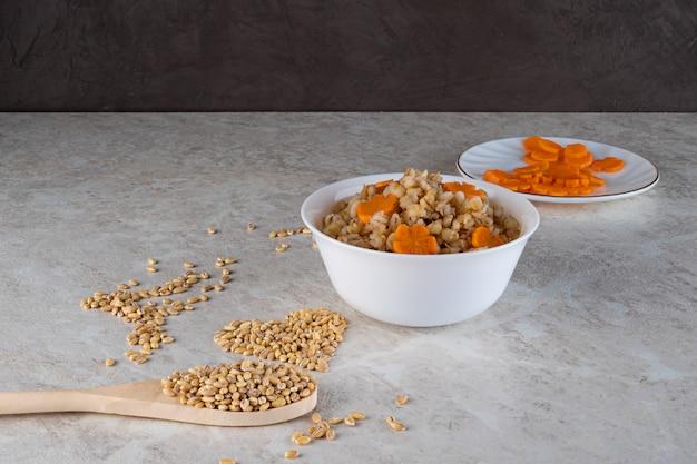 Bouillie d'épeautre dans un bol blanc et décorée d'une carotte astérisque, alimentation diététique.