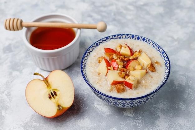 Bouillie de flocons d'avoine dans un bol avec des tranches de miel et de pomme rouge, vue de dessus
