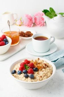 Bouillie de flocons d'avoine avec myrtille, framboises, vue latérale, vertical. petit-déjeuner sain avec des baies