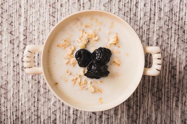 Bouillie de flocons d'avoine avec des prunes noires sèches dans le bol