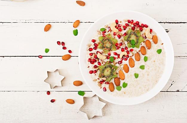 Bouillie de gruau savoureuse et saine avec kiwi, grenade et graines. petit-déjeuner sain. nourriture de fitness. nutrition adéquat. vue de dessus