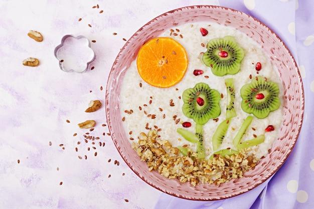 Bouillie de gruau savoureuse et saine avec kiwi, grenade et noix. petit-déjeuner sain. nourriture de fitness. nutrition adéquat. vue de dessus