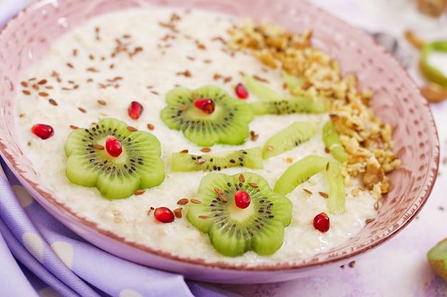 Bouillie de gruau savoureuse et saine avec kiwi, grenade et noix. petit-déjeuner sain. nourriture de fitness. nutrition adéquat.