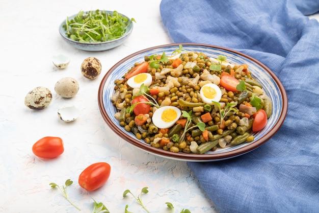 Bouillie de haricot mungo avec des œufs de caille, des tomates et des germes micro-verts sur un fond de béton blanc. vue latérale, gros plan.