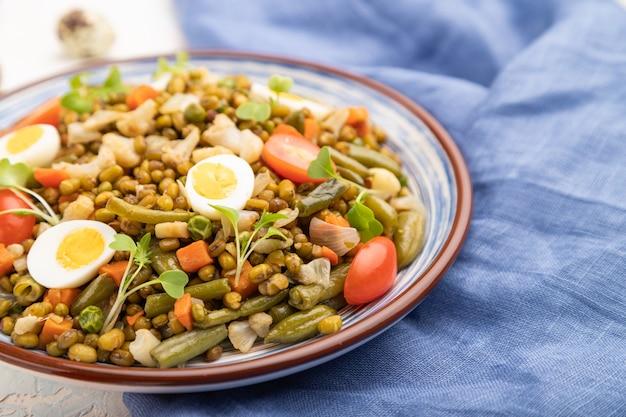 Bouillie de haricot mungo avec des œufs de caille, des tomates et des germes micro-verts sur un fond de béton blanc.