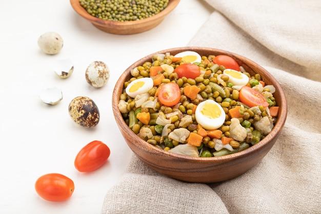 Bouillie de haricot mungo avec des œufs de caille, des tomates et des germes micro-verts sur un fond en bois blanc. vue latérale, gros plan.