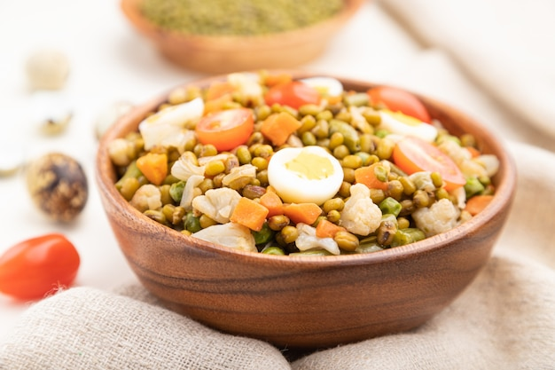 Bouillie de haricot mungo avec des œufs de caille, des tomates et des germes micro-verts sur un fond en bois blanc.