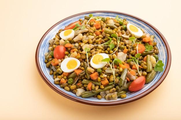 Bouillie de haricot mungo avec des œufs de caille, des tomates et des germes micro-verts sur fond orange pastel. vue de côté.