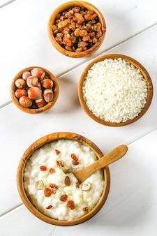 Bouillie de lait de riz aux noix et raisins secs dans des bols en bois sur une table en bois blanche