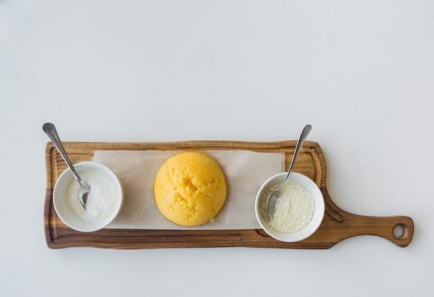 Bouillie de maïs roumaine mamalyga avec du fromage et de la crème sure sur un support en bois.