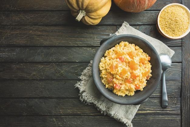 Bouillie de millet à la citrouille douce dans un bol, style rustique. plat végétalien sain. vue de dessus