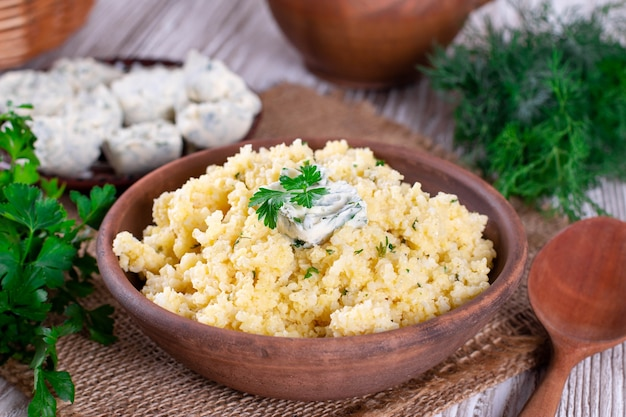 Bouillie de millet avec du beurre et du persil dans une assiette en céramique sur une table en bois