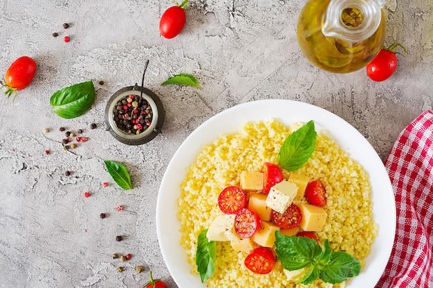 Bouillie de millet avec fromage, beurre et basilic dans un bol blanc. nourriture savoureuse. petit déjeuner.