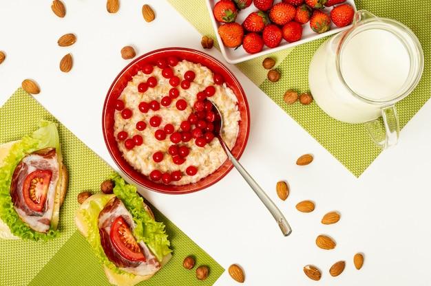 Bouillie plate avec des fruits et des sandwiches sur fond uni