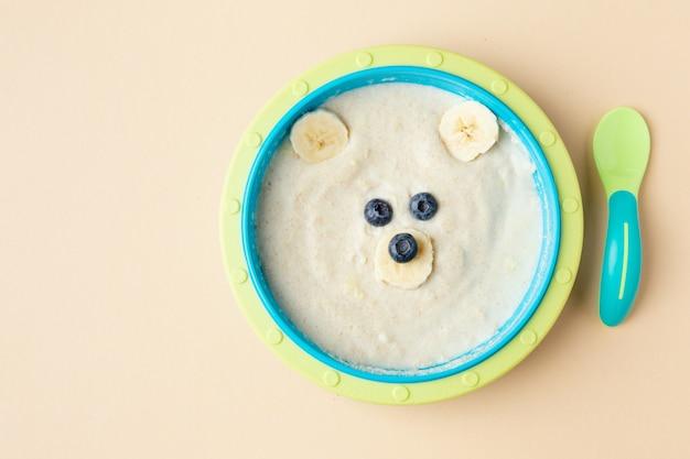 Bouillie pour bébé à l'avoine, banane et baies sur assiette. vue de dessus avec espace de copie.