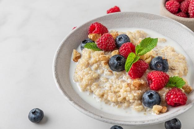 Bouillie de quinoa aux bleuets frais, framboises, noix et menthe dans un bol sur fond blanc. fermer. petit déjeuner alimentation saine