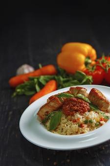 Bouillie de riz avec des légumes et de la viande sur une table en bois noire.
