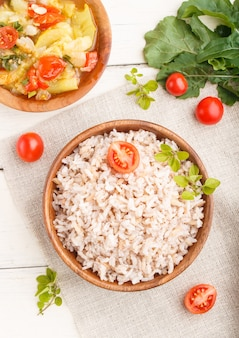 Bouillie de riz non poli avec des légumes cuits et l'origan dans un bol en bois sur une surface en bois blanche. vue de dessus, gros plan.