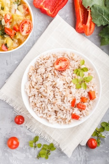 Bouillie de riz non polie avec des légumes cuits et l'origan dans un bol blanc sur une surface en béton gris. vue de dessus, gros plan.