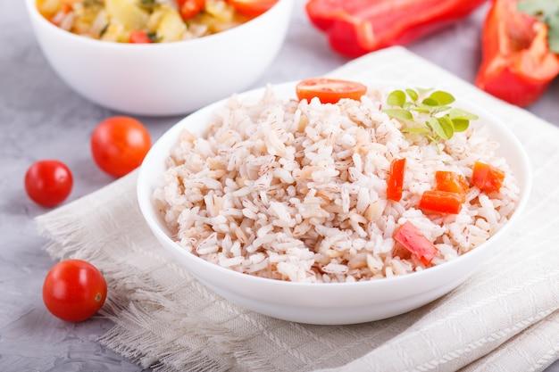 Bouillie de riz non polie avec des légumes cuits et l'origan dans un bol blanc. vue latérale, gros plan.