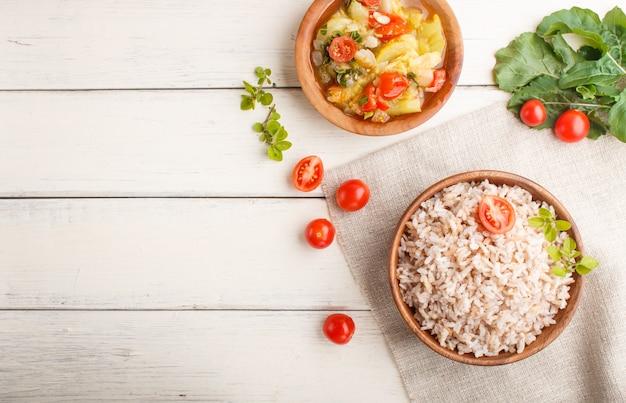 Bouillie de riz non polie avec légumes cuits à l'origan et origan dans un bol en bois sur un fond en bois blanc