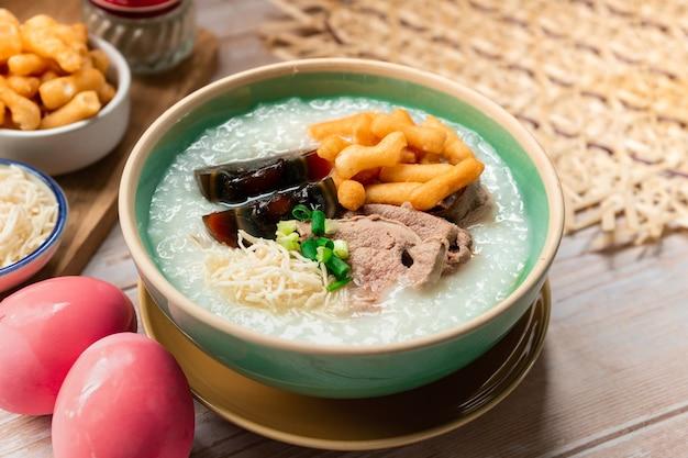 Bouillie de riz à la thaïlandaise avec œuf du siècle et garniture d'œuf à la coque avec patongo et petit-déjeuner de nouilles croustillantes