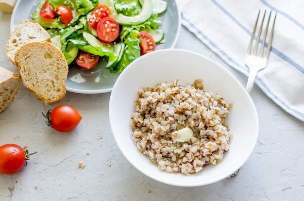 Bouillie de sarrasin chaude avec du beurre fondant dans une assiette blanche et une salade de légumes pour le lanch sur la table, vue de dessus, espace de copie concept d'alimentation saine