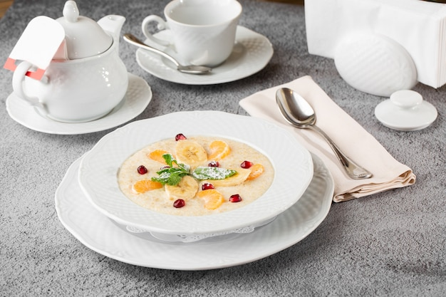 Bouillie de semoule ou flocons d'avoine avec des bananes en tranches dans un bol blanc isolé sur une table en pierre grise. nourriture faite maison. petit déjeuner savoureux. mise au point sélective. photo horizontale. tasse et théière.