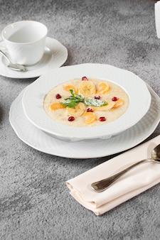 Bouillie de semoule ou flocons d'avoine avec des bananes en tranches dans un bol blanc isolé sur une table en pierre grise. nourriture faite maison. petit déjeuner savoureux. mise au point sélective. photo verticale. tasse et théière.