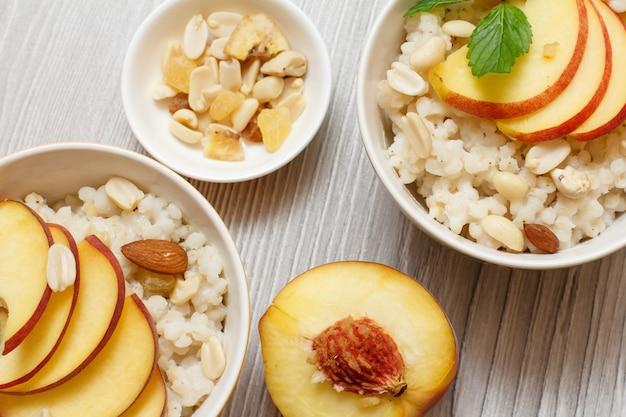 Bouillie de sorgho avec morceaux de pêche, noix de cajou et amande dans des bols en porcelaine, une pêche fraîche sur les planches de bois gris. salade de sorgho végétalienne sans gluten aux fruits.