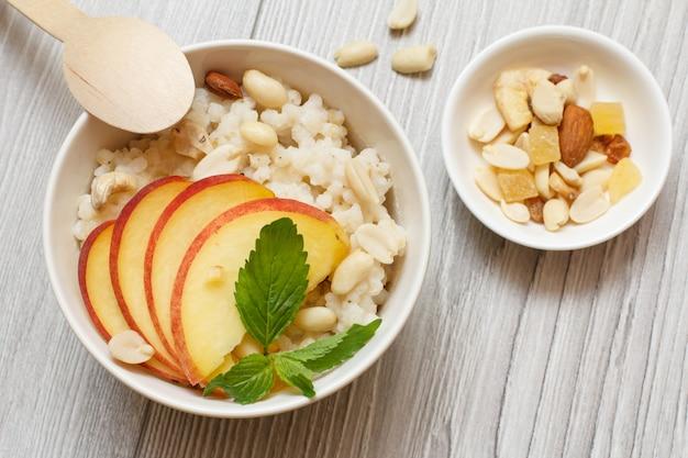 Bouillie de sorgho avec morceaux de pêche, noix de cajou et amandes dans des bols en porcelaine, une cuillère en bois sur les planches grises. salade de sorgho végétalienne sans gluten aux fruits.