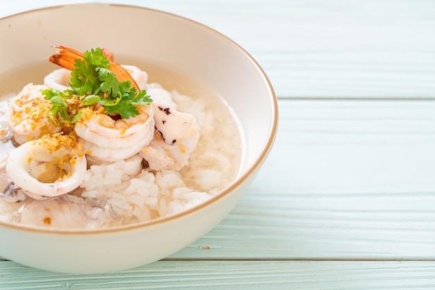 Bouillie ou soupe de riz bouillie avec bol de fruits de mer (crevettes, calamars et poisson)