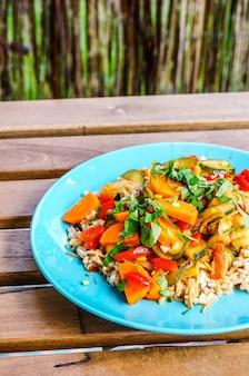 Une bouillie avec de la viande de poulet et des légumes frais coupés sur une plaque bleue sur une table en bois