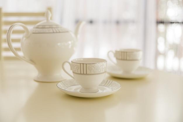 Bouilloire blanche et deux tasses à thé sur la table.