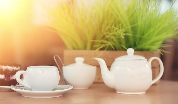 Bouilloire avec une boisson et un dessert au café de la rue. thé dans la tasse de bouilloire sur la table. petit déjeuner avec thé et gâteaux au café.
