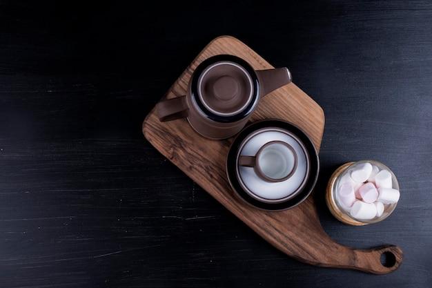 Bouilloire à café avec une tasse et des guimauves sur un plateau en bois sur fond noir.