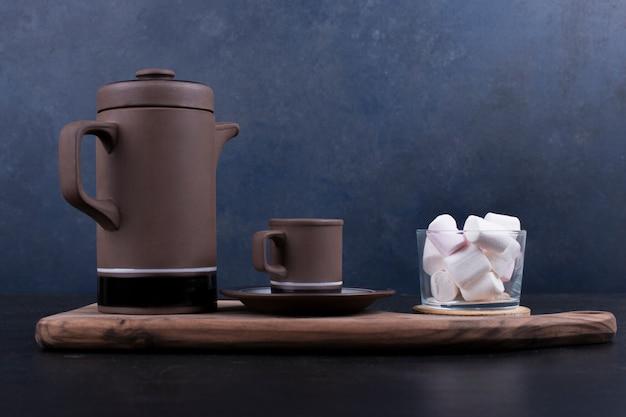 Bouilloire à café avec une tasse et des guimauves sur un plateau en bois, vue de profil.