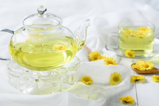 Bouilloire de chrysanthème et chrysanthème chaud dans une tasse sur un tissu blanc et bois blanc