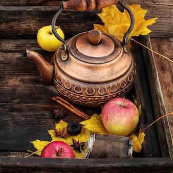 Bouilloire en cuivre et feuilles d'automne