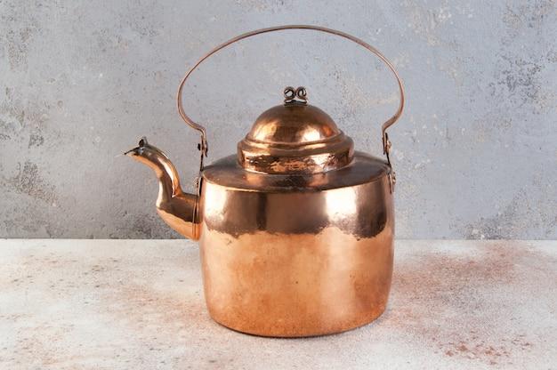 Bouilloire en cuivre vintage sur fond de béton.