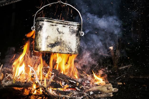 La bouilloire sur le feu de camp au camping dans la nature la nuit